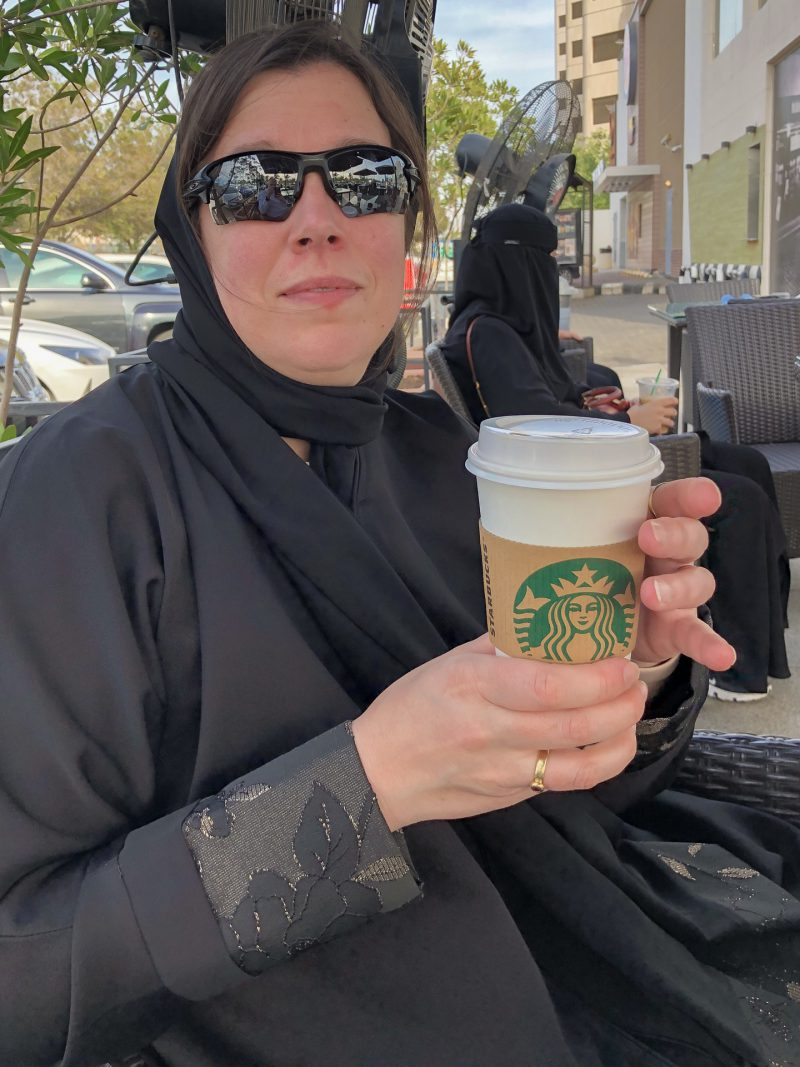 Veschleierte Frau mit Kaffe-to-Go