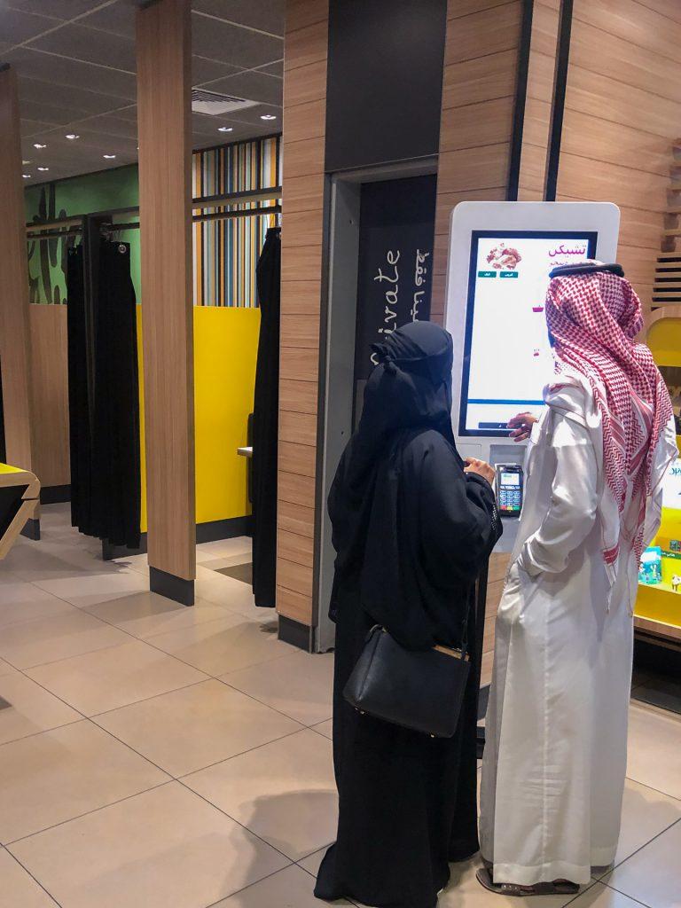 Fast-Food Bestell-Terminal mit einem Saudi-Paar (sie voll verschleiert, er im traditionellen Gewand)